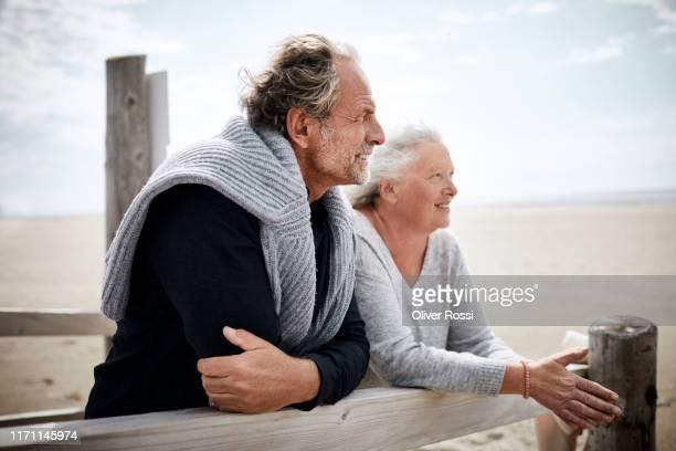 senior couple standing on boardwalk on the beach - coppia anziana foto e immagini stock