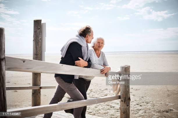senior couple standing on boardwalk on the beach - pensionierung stock-fotos und bilder