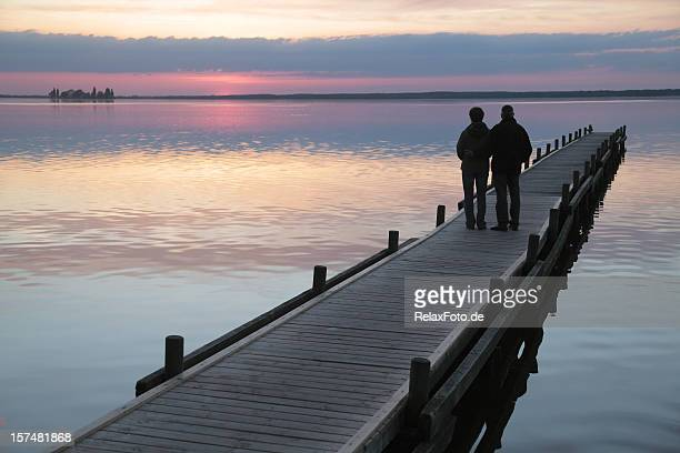 senior couple standing on lakeside jetty at sunset (xxxl) - jetty stock pictures, royalty-free photos & images