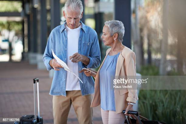 Senior couple standing on public transport station, looking at map