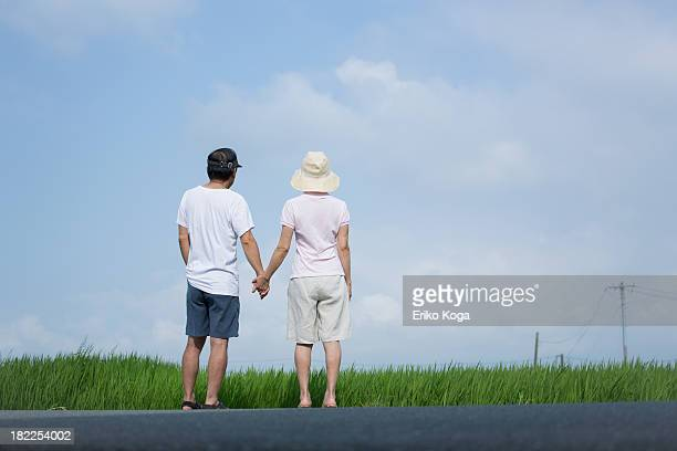 Senior Couple Standing on Road and Looking at Sky
