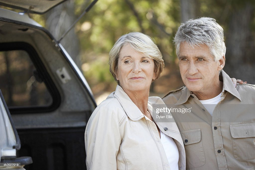 Senior Couple Standing Side by Side in a Forest With an SUV in the Background : Stock Photo