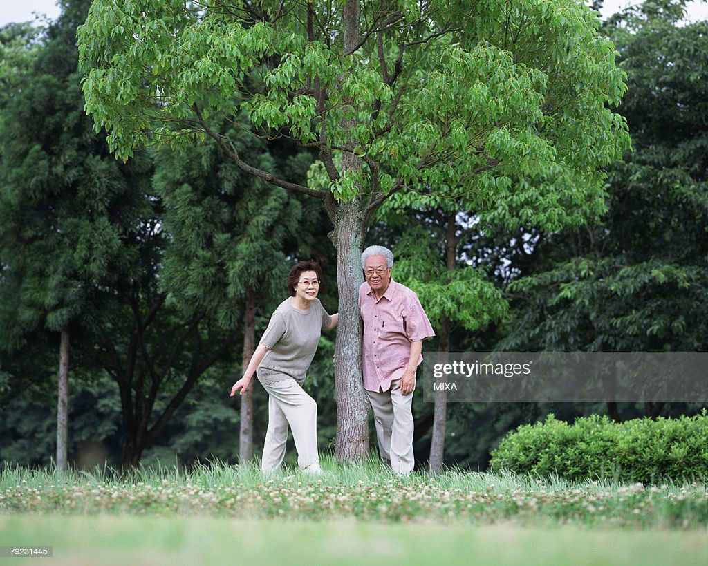 Senior couple standing under tree : Stock Photo
