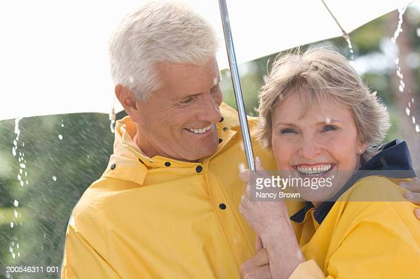 Senior couple standing under umbrella in rain, smiling, close-up