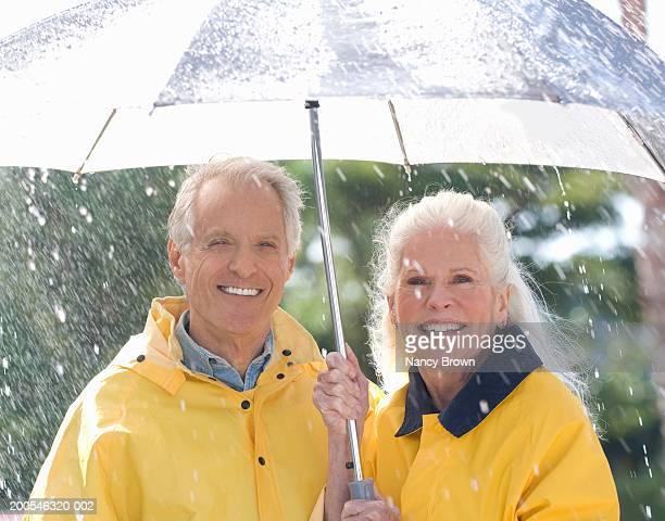 Senior couple standing under umbrella in rain, smiling, portrait