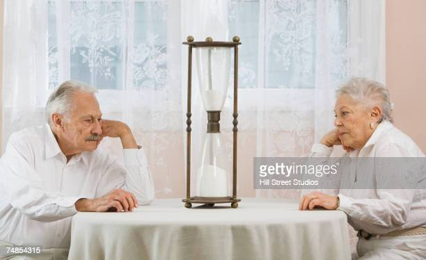 senior couple staring at hourglass - permanente - fotografias e filmes do acervo
