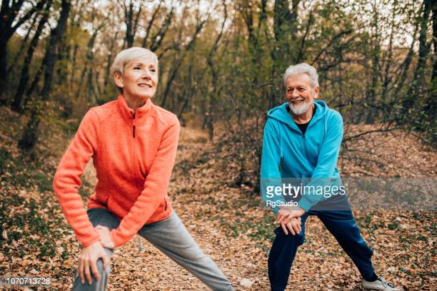 Senior couple stretching legs in a park