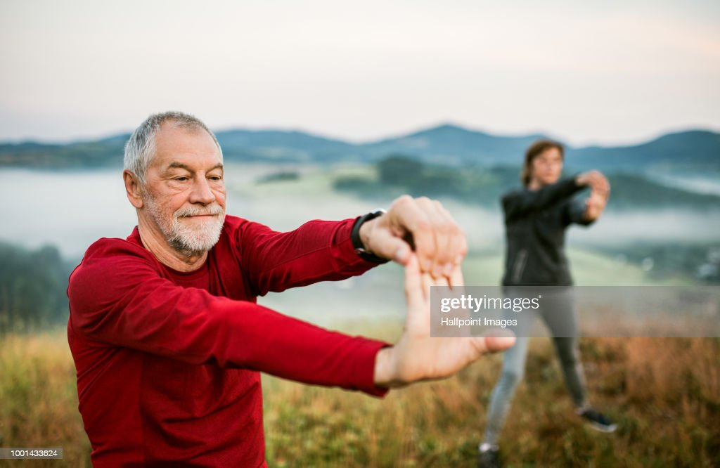 Senior couple stretching outdoors in nature in the foggy morning. : Stock Photo