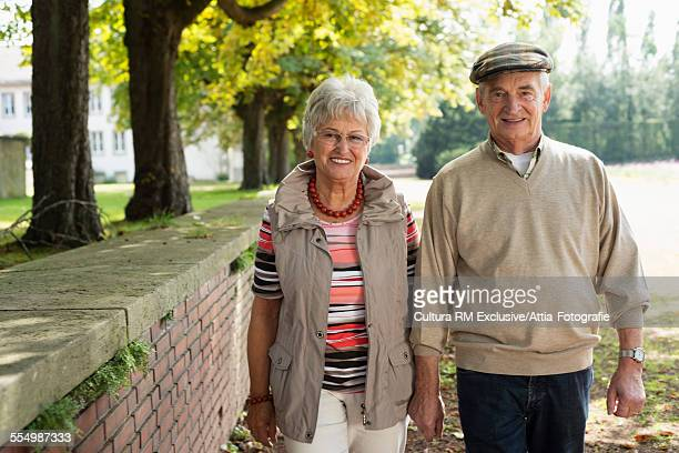 Senior couple strolling hand in hand in park