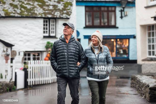 senior couple strolling through town - rain stock pictures, royalty-free photos & images