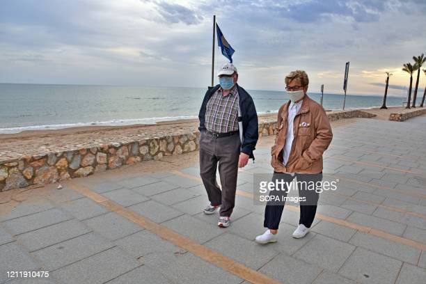 A senior couple strolls along the beach while wearing a face mask as a precaution against the covid19 during the schedule stipulated time Seniors...