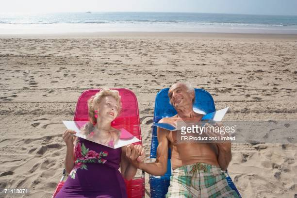 senior couple sunning themselves at the beach - sunbathing stock pictures, royalty-free photos & images