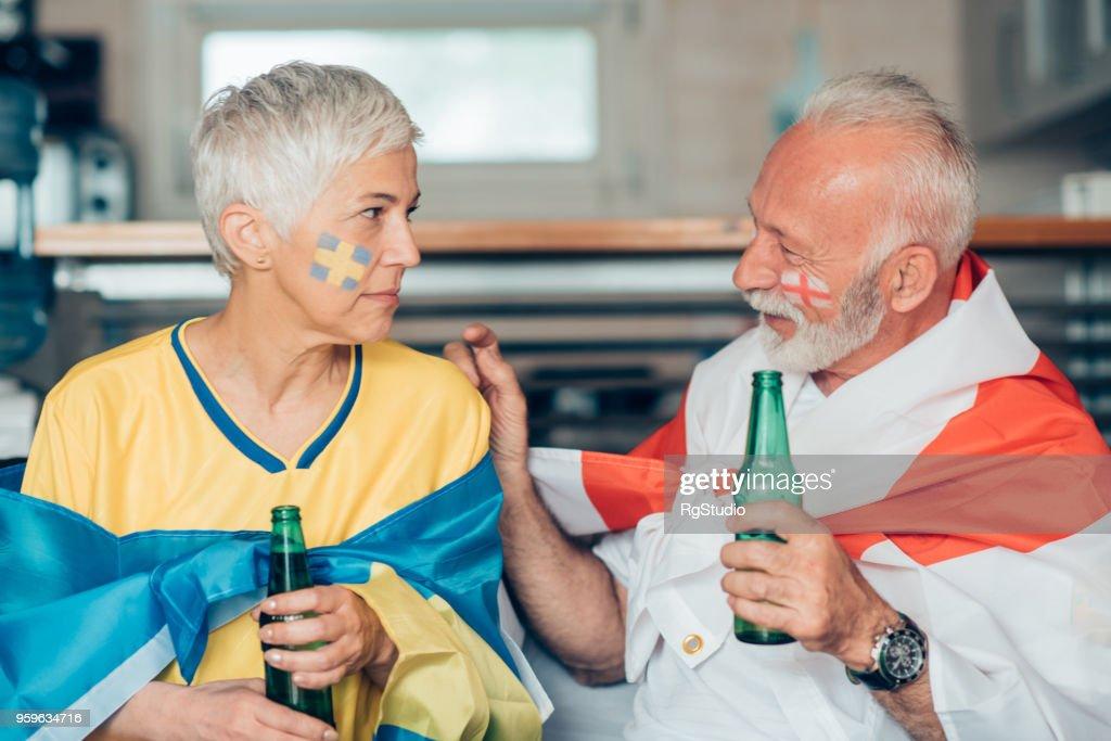Älteres Paar unterstützt verschiedene Fußballmannschaften sahen einander : Stock-Foto