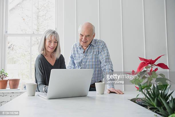 Senior couple surfing the net on laptop at home together