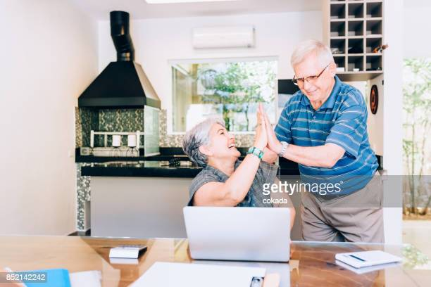 senior couple surfing the web and cheering - surfing the net stock pictures, royalty-free photos & images