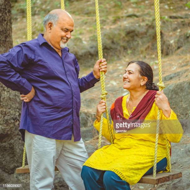 senior couple swings in their summer vacation. - carefree stock pictures, royalty-free photos & images
