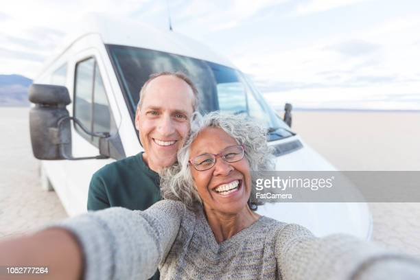 senior couple takes a selfie on their road trip through the desert! - road warrior stock photos and pictures