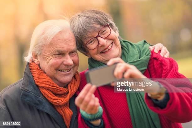 senior paar neemt een selfie samen - menselijke relaties stockfoto's en -beelden
