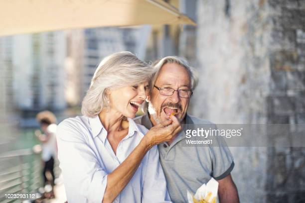 senior couple taking a city break, eating french fries - pareja hombre mayor y mujer joven fotografías e imágenes de stock