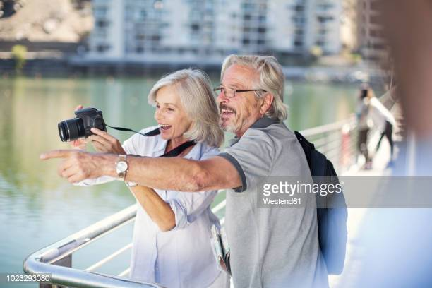 senior couple taking a city break, taking photos - pointing at camera stock photos and pictures