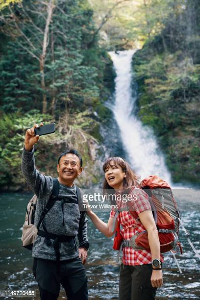 Senior couple taking a selfie with a smart phone in front of a waterfall while hiking in a forest
