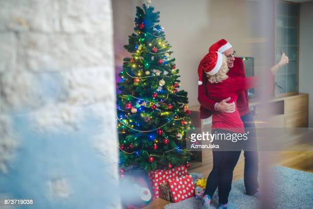 senior couple taking a selfie with christmas present - photo messaging stock photos and pictures