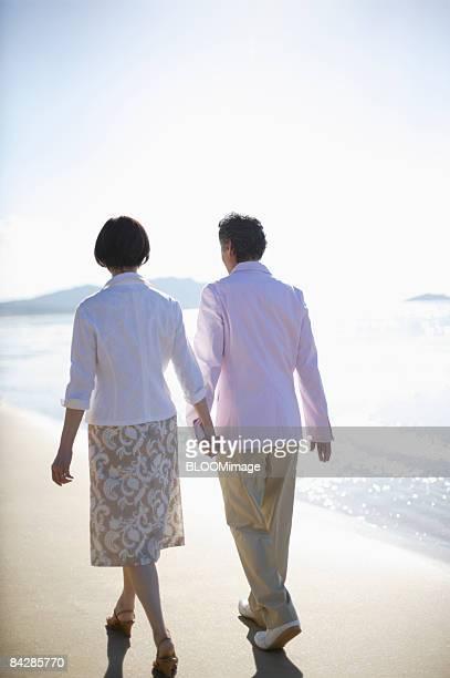 Senior couple taking a walk hand in hand at beach, rear view