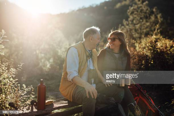 senior couple taking break from hiking - baby boomer stock pictures, royalty-free photos & images
