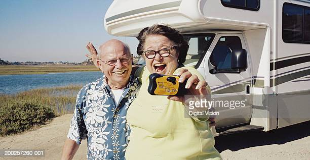 Senior couple taking photo of themselves by camper van