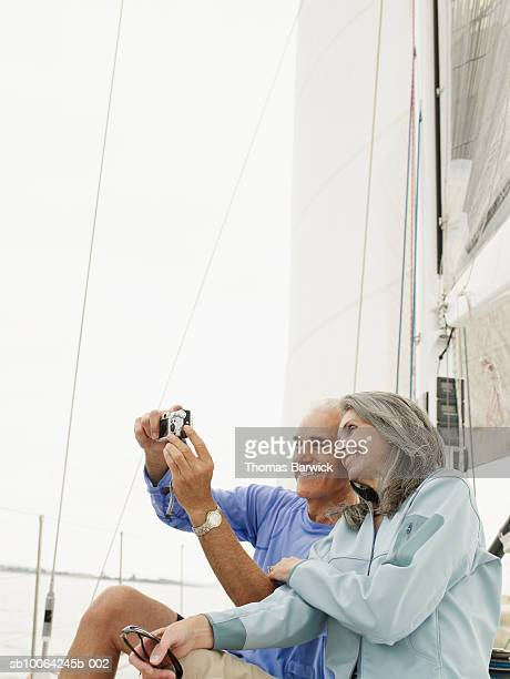 Senior couple taking photograph of selves on sailboat