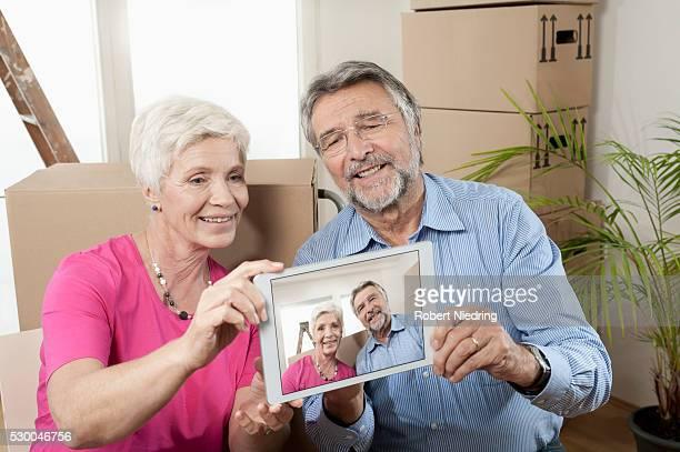 Senior couple taking photographs on digital phone in new apartment, Bavaria, Germany