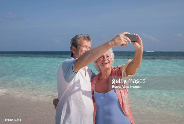 senior couple taking pictures on the beach - vilamendhoo stock photos and pictures