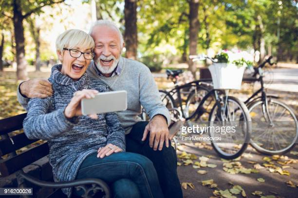 senior couple taking selfie in the park - active seniors stock pictures, royalty-free photos & images
