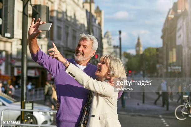 Senior couple taking selfie on street in city
