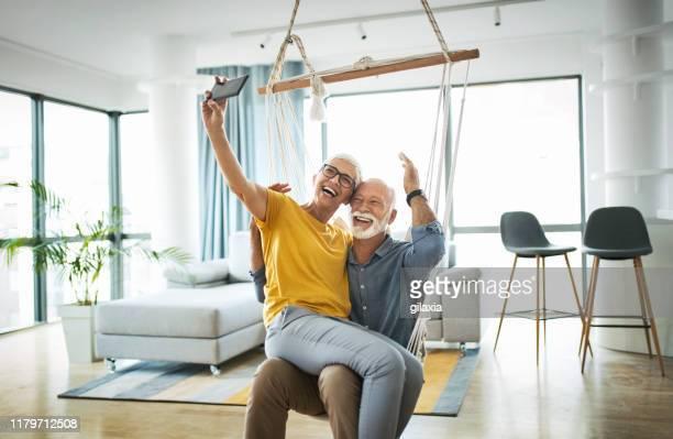 senior couple taking selfies at home. - gilaxia foto e immagini stock