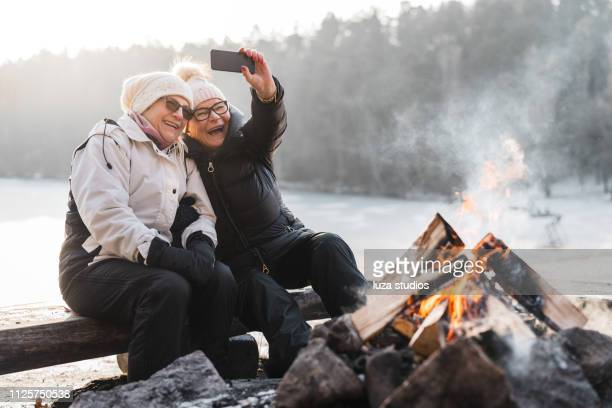 senior couple taking selfies by the campfire - joy stock pictures, royalty-free photos & images