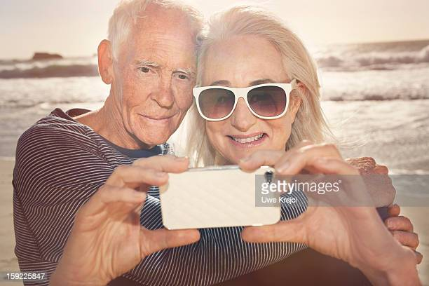 Senior couple taking self-portrait with phone