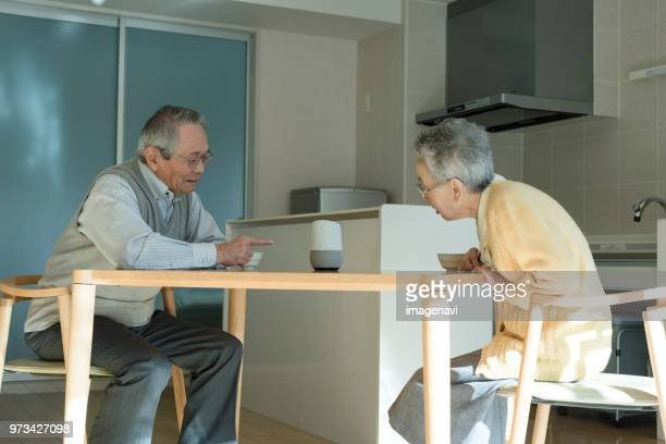 Senior couple talking to AI speaker