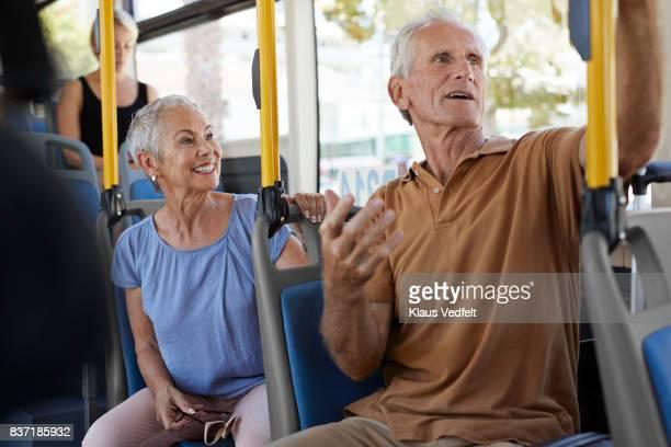 Senior couple talking together on public bus