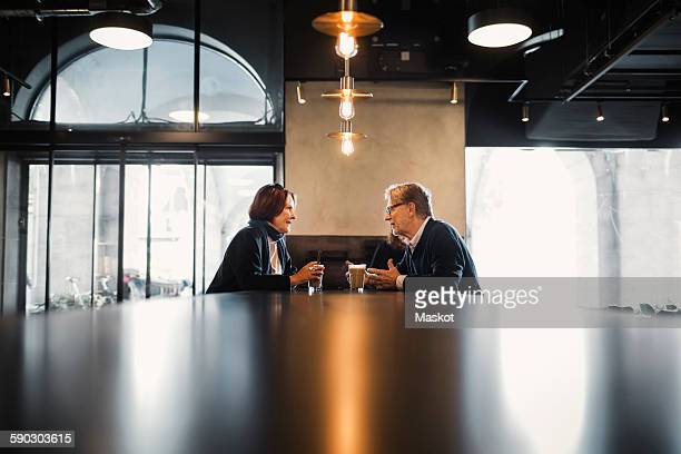 senior couple talking while having coffee at cafeteria - 向かい合わせ ストックフォトと画像