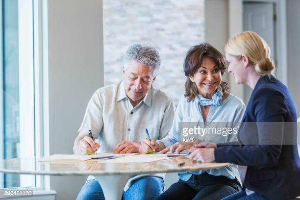 senior couple talking with a personal advisor, signing papers - signing stock pictures, royalty-free photos & images