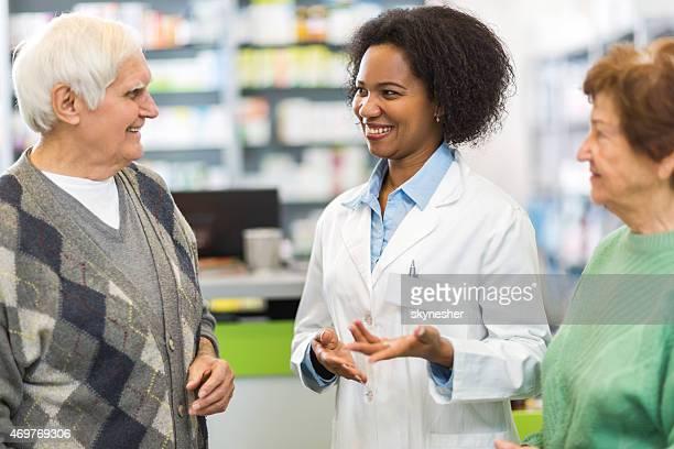 Senior par hablar con afroamericana farmacéutico.