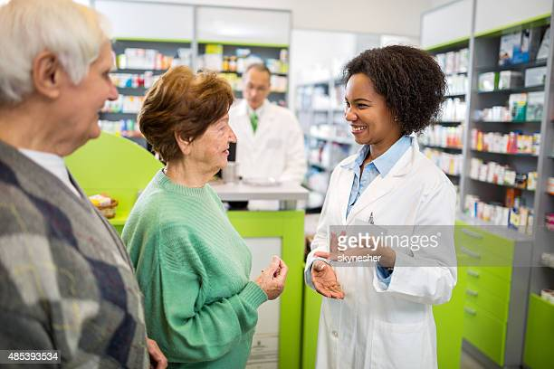 Senior couple talking with African American pharmacist.