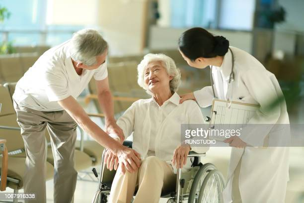 senior couple talking with doctor - 公共の建物 ストックフォトと画像