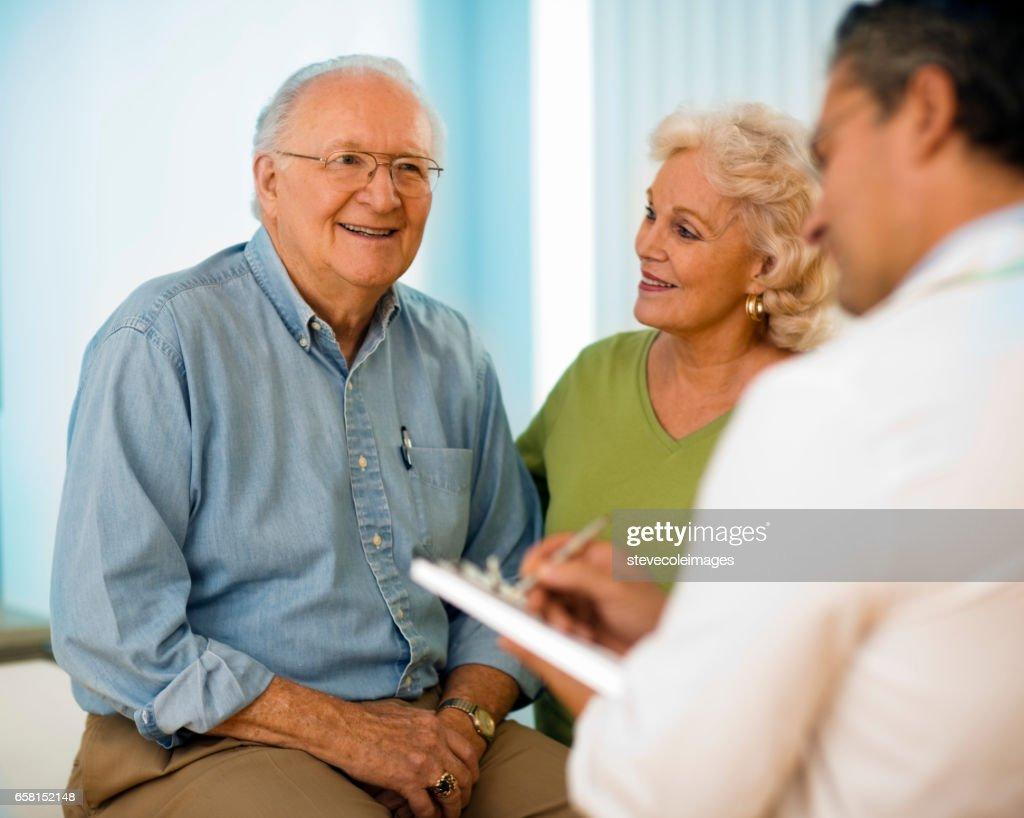 Senior couple talking with doctor. : Stock Photo