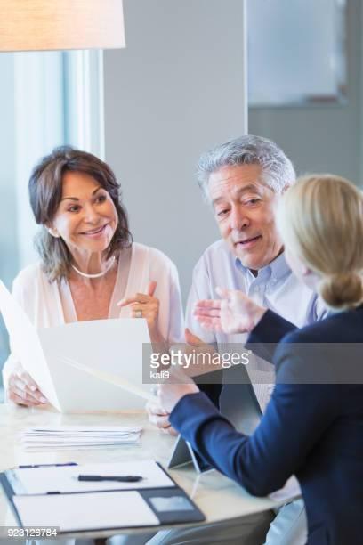 Senior couple talking with financial advisor