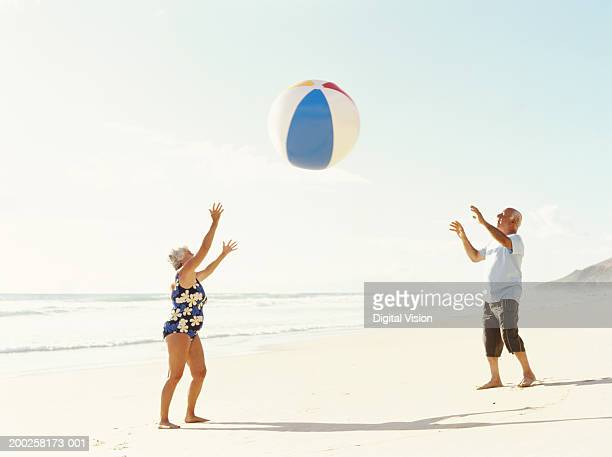Senior couple throwing beach ball on beach