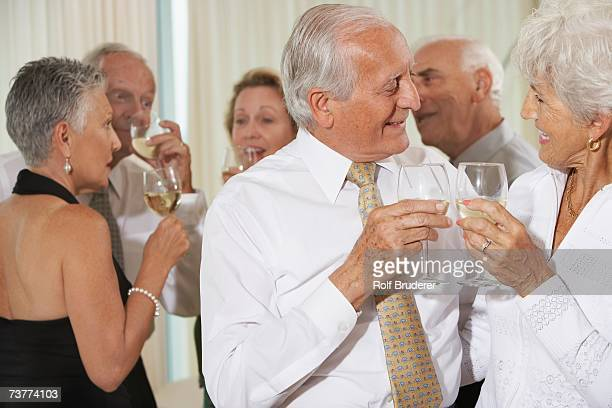 Senior couple toasting at party with friends in background