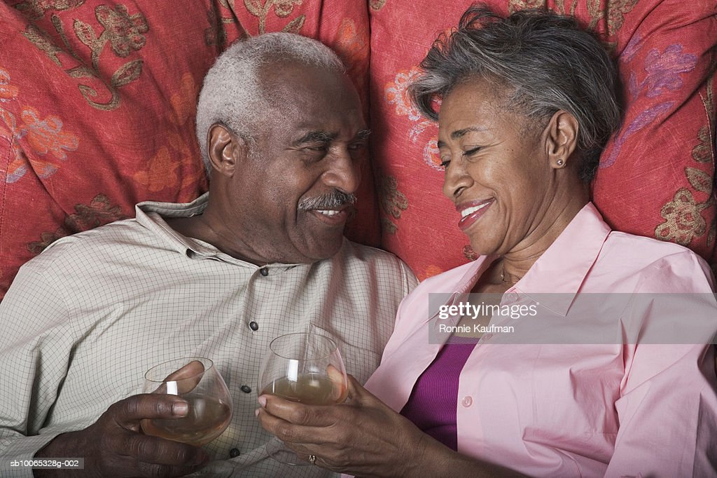 Senior couple toasting champagne on bed : Foto stock