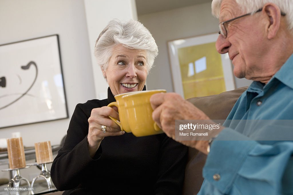 Senior couple toasting coffee mugs : Foto stock